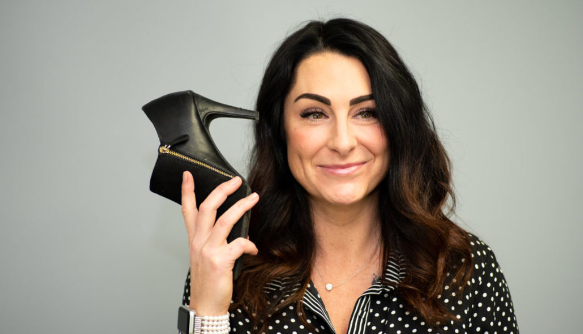 better business podcast host kelli rae holding shoe like a phone